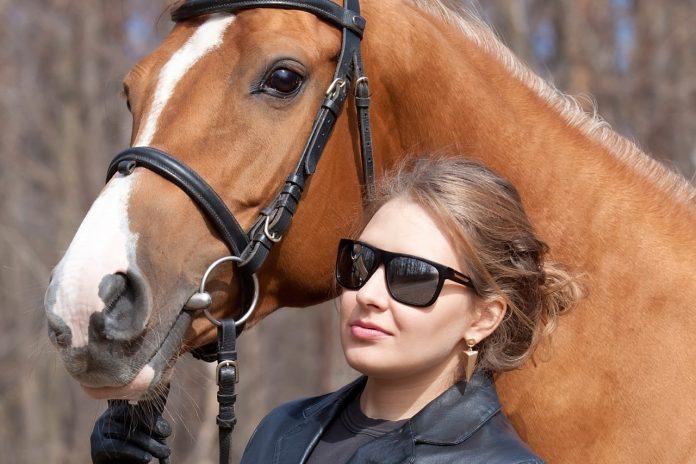 Kvinde med solbriller på står samme med hest