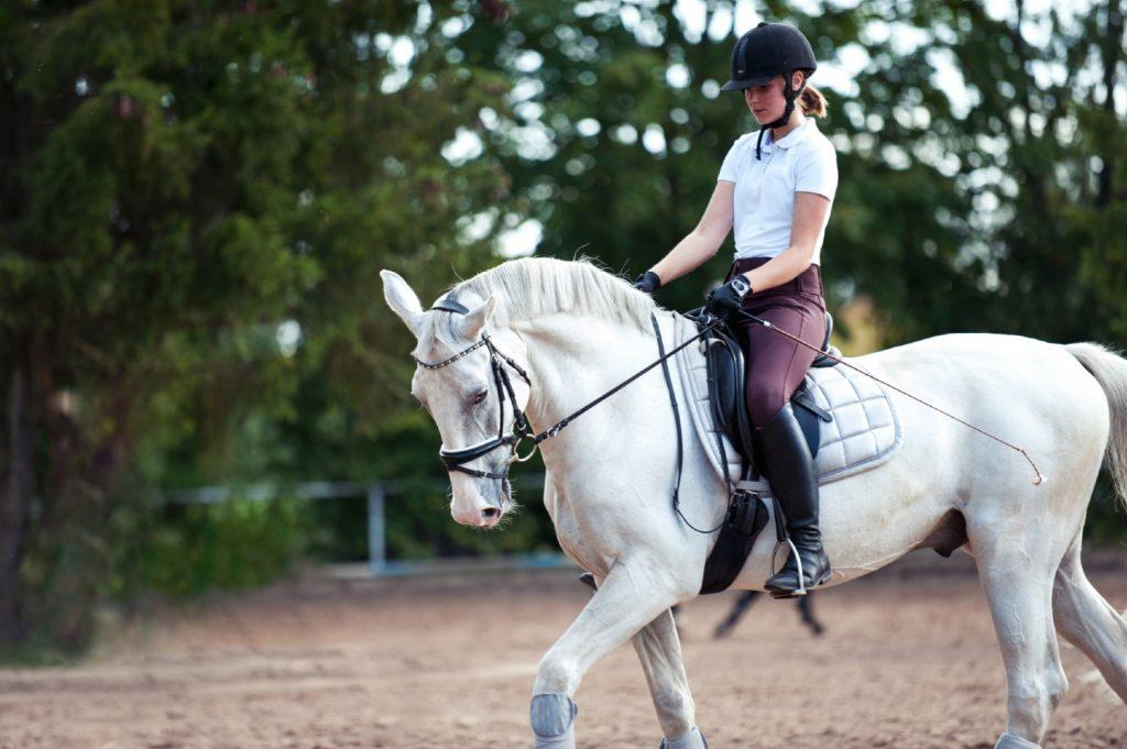 En pige, der rider dressur på en hvid hest.