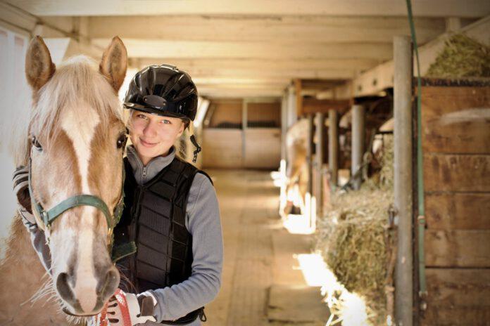 hest og rytter i stald