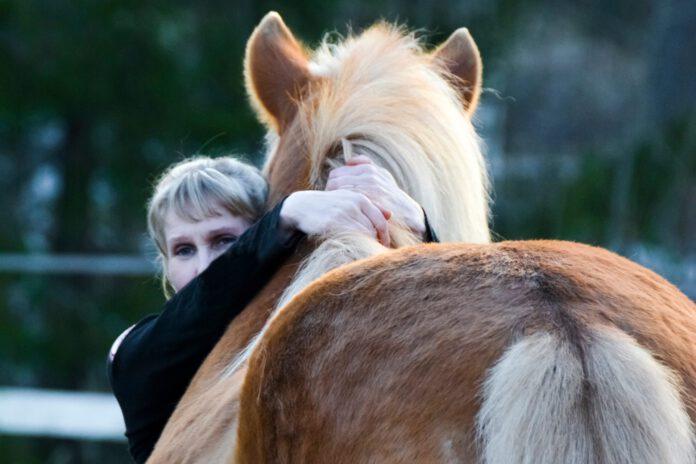 Kvinde krammer hest fordi hun skal tage en vigtig beslutning