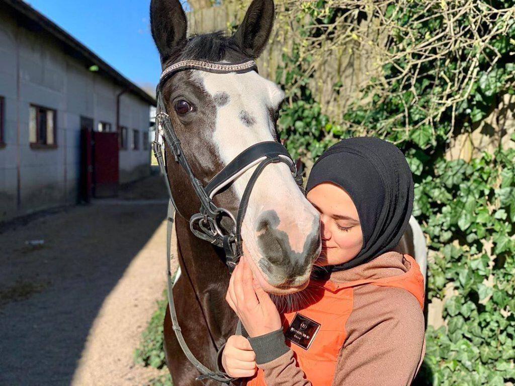 Rytter Rim Al-Attar står med sin hest.