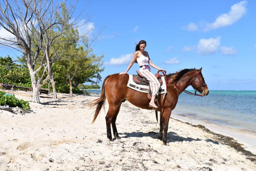 Mathilde fra World On Horseback på en hest, på en strand i Cayman Islands.