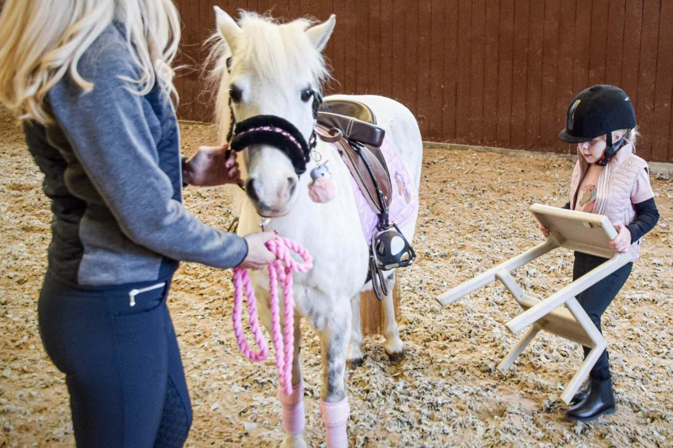 Barn bærer skammel hen til sin pony, imens en forælder holder ponyen
