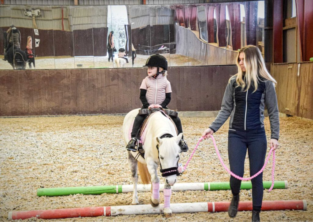 Et barn træner sin hest i ridehus med hjælp fra en forælder