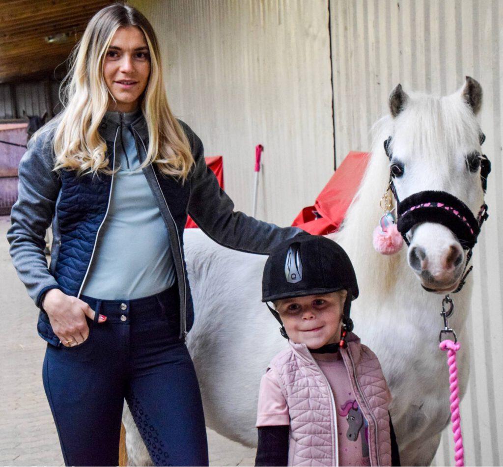 Mor, børn og heste på staldgang
