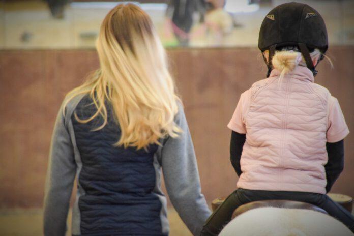 Barn rider og voksen trækker