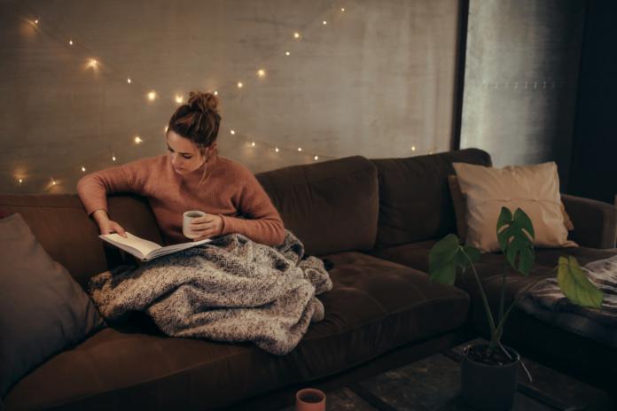 Kvinde læser bog i sofa.