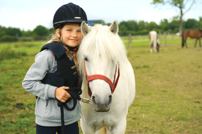 Pige med pony på rideskole